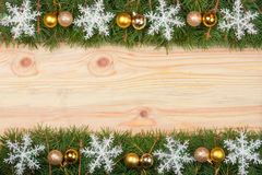 Il Natale incornicia fatto dei rami dell'abete decorati con i fiocchi di neve e le palle dell'oro su un fondo di legno leggero Fotografie Stock