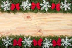 Il Natale incornicia fatto dei rami dell'abete decorati con i fiocchi di neve ed il rosso si piega su un fondo di legno leggero Fotografia Stock Libera da Diritti