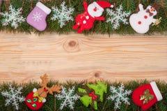 Il Natale incornicia fatto dei rami dell'abete decorati con i fiocchi di neve pupazzo di neve e Santa Claus su un fondo di legno  Fotografia Stock