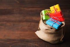 Il Natale insacca con i presente variopinti sopra fondo di legno Immagini Stock