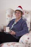 Il natale maggiore maturo della donna intrattiene il cappello della Santa Fotografia Stock