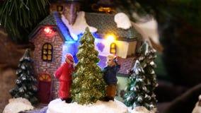 Il Natale miniatura ha decorato le case con le figure ballanti intorno all'abete di Natale archivi video