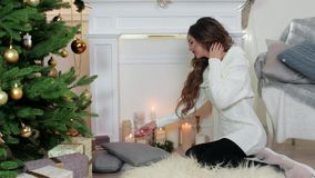 Il Natale, ragazza accende una candela che si siede dal camino vicino all'albero di Natale, bella giovane donna nell'accogliente  stock footage