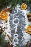Il Natale rappresenta, numero 2018 è scritto con farina su un fondo scuro immagine stock