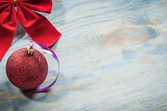 Il Natale rosso annoda la bagattella sulle feste co dello spazio della copia del bordo di legno Immagini Stock Libere da Diritti
