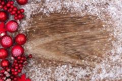 Il Natale rosso orna il confine laterale con neve su legno rustico Immagini Stock