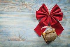 Il Natale rosso piega la bagattella dorata sul raggiro delle celebrazioni del bordo di legno Immagine Stock