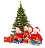 Il Natale scherza in cappello di Santa con i presente che si siedono nell'ambito del tre dell'abete Fotografia Stock