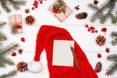 Il Natale segna sul fondo di festa con il cappello rosso di Santa, rami dell'abete, pigne, decorazioni rosse Disposizione piana,  Immagini Stock Libere da Diritti