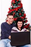 Il Natale si accoppia con il computer portatile immagine stock