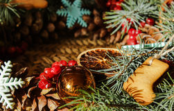 Il Natale si avvolge con i biscotti dello zenzero e l'abete rosso blu sui pezzi incisi cotogne del fondo della paglia Fotografia Stock