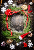 Il Natale si avvolge, fiocchi di neve, nastro rosso e varie decorazioni dell'inverno su fondo di legno rustico Immagine Stock