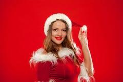 Il Natale si chiude sul ritratto di bella ragazza sexy che indossa i vestiti del Babbo Natale, sopra fondo rosso immagine stock libera da diritti