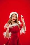 Il Natale si chiude sul ritratto di bella ragazza sexy che indossa i vestiti del Babbo Natale, sopra fondo rosso immagine stock