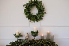 Il Natale verde si avvolge con le decorazioni sulla parete bianca Fotografia Stock Libera da Diritti