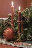 Il Natale visualizza la mostra delle candele rosse nei supporti d'ottone Fotografia Stock Libera da Diritti