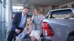 Il negozio automatico, ritratto della famiglia felice con la figlia sceglie l'automobile e si consulta a vicenda mentre si siede