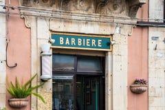 Il negozio di barbiere firma dentro Palazzolo Acreide, Siracusa, Sicilia, Italia Immagini Stock