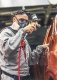 Il negozio di pittura della carrozzeria degli impiegati effettua l'elemento della pittura immagine stock