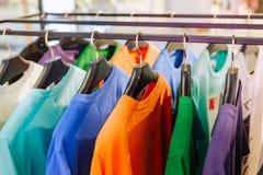 Il negozio di vestiti sta i ganci colorati delle camice fotografia stock libera da diritti