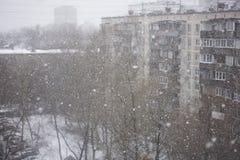 Il neige en dehors de la fenêtre sur le fond de la ville Photographie stock libre de droits
