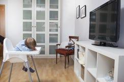 Il neonato è caduto addormentato sul suo seggiolone Immagini Stock