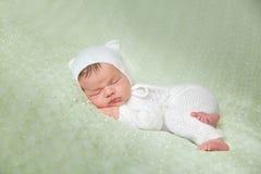 Il neonato addormentato sveglio nel bianco ha tricottato il costume lanuginoso del gattino fotografie stock libere da diritti