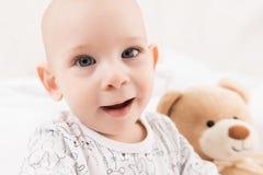 Il neonato adorabile che si siede su un letto, giocante con il giocattolo riguarda un letto Rilassamento del bambino neonato immagini stock