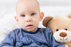 Il neonato adorabile che si siede su un letto, giocante con il giocattolo riguarda un letto Ritratto del bambino neonato fotografia stock libera da diritti