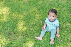 Il neonato asiatico gode di di mangiare il pollo fritto nel giardino verde all'aperto fotografie stock