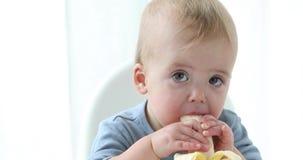 Il neonato attraente mangia una banana stock footage