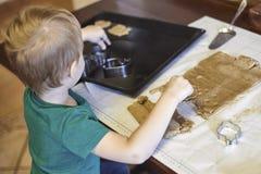 Il neonato caucasico sveglio aiuta in cucina, facente i coockies Stile di vita casuale in bambino interno e grazioso domestico da fotografia stock