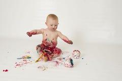 Il neonato che gioca con casalingo fingerpaints Immagini Stock