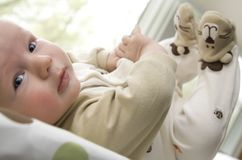 Il neonato che si trova sopra appoggia con i piedi in su nell'aria Fotografie Stock Libere da Diritti