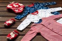 Il neonato copre (sleepsuits, cappello tricottato e guanti) su marrone Immagini Stock