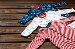 Il neonato copre (sleepsuits) su fondo di legno marrone Fotografie Stock