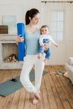Il neonato della tenuta della madre su lei armi e aspetta a pratica di yoga Immagini Stock