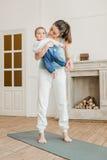 Il neonato della tenuta della madre su lei armi e aspetta a pratica di yoga Immagini Stock Libere da Diritti