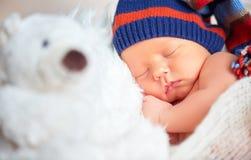 Il neonato dentro tricotta il sonno dell'orso del giocattolo dell'orsacchiotto e del cappuccio Fotografia Stock Libera da Diritti