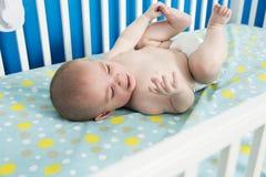 Il neonato di un mese sveglio sta mettendola su indietro nella greppia, gridante Immagini Stock