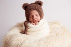 Il neonato dolce in orso complessivo, dormendo a letto con l'orsacchiotto farcito gioca, paesaggio dell'inverno dietro lui immagini stock