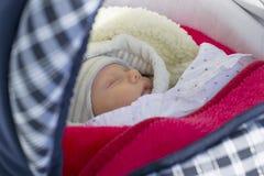 Il neonato dorme su una passeggiata in una carrozzina un giorno di inverno fotografie stock