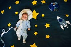 Il neonato dorme sui precedenti del cielo stellato con un razzo e un pianeta Fotografie Stock