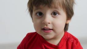 Il neonato in maglietta rossa su fondo bianco ha giocato archivi video