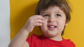 Il neonato in maglietta rossa su fondo giallo ha giocato video d archivio