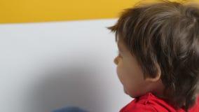 Il neonato in maglietta rossa su fondo giallo ha giocato stock footage