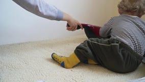 Il neonato sta giocando con l'aspirapolvere finché la madre non sia aspirazione archivi video
