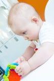 Il neonato sta giocando con un giocattolo mentre si sedeva Fotografie Stock