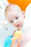 Il neonato sta giocando con un giocattolo mentre si sedeva Fotografia Stock Libera da Diritti