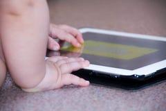 Il neonato sta sedendosi sul pavimento che gioca con il pc della compressa Foto del primo piano delle mani Poco cuscinetto di toc Immagini Stock Libere da Diritti